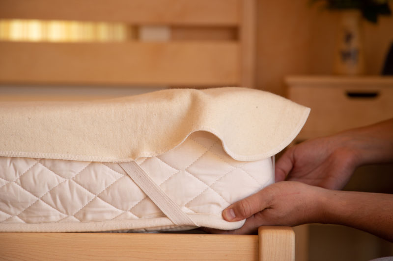 Washable Wool Mattress Protector on Latex Mattress with hands adjusting