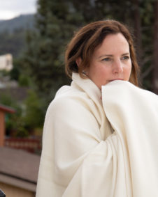 Organic Merino Wool Blanket wrapped around Shepherd's Dream owner Robin Kearns.