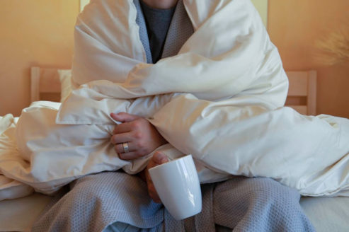 Model wrapped in wool comforter with white coffee mug