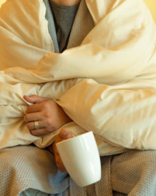 Close up of model wrapped in wool comforter with white ceramic mug and wedding ring