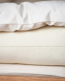 Up close photo of hand made wool bedding featuring wool mattress and wool topper