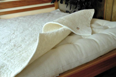Undyed ivory felt positioned on a wool mattress.