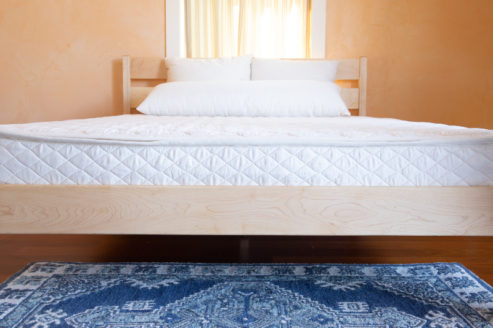 Head on shot of All Natural Latex Mattress in quilted wool and organic cotton encasement on maple Classic frame