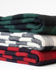 Three buffalo plaid blankets, stacked: red, ivory, and green