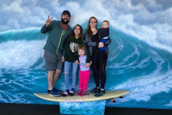 Shepherd's Dream Marketing Director Eric Smith with his family. Family is perched on a surfboard against an illustration of a wave. From left to right: Eric, his two daughters, his wife, and his baby son.