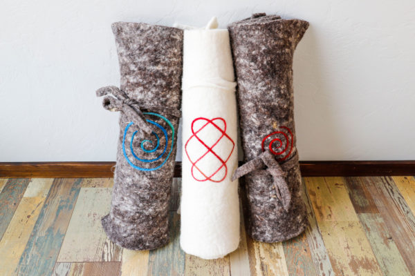 Rolled Yoga Felts on Display: two marbled and one ivory